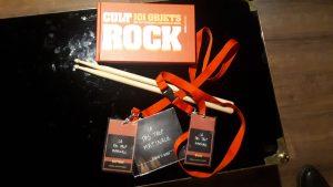 """Accessoires du Rockstar Tour : baguettes de batteries, livre sur les objets cultes du rock, pass du groupe """"La Pas Trop Matinale"""", CD du groupe """"La Pas Trop Matinale""""."""